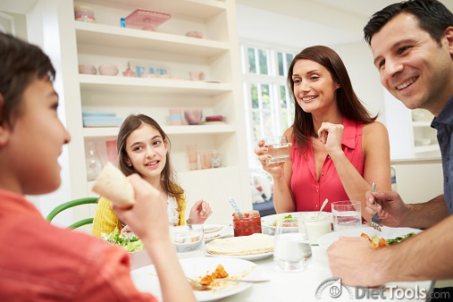 Hispanic Family Sitting At Table Eating Meal Together