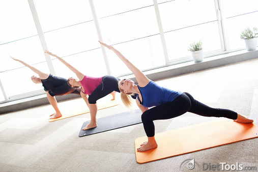 Young people holding triangle pose in a yoga class