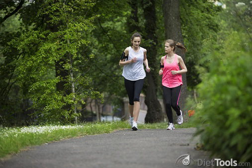 Two sporty women running outdoors in a natural setting.